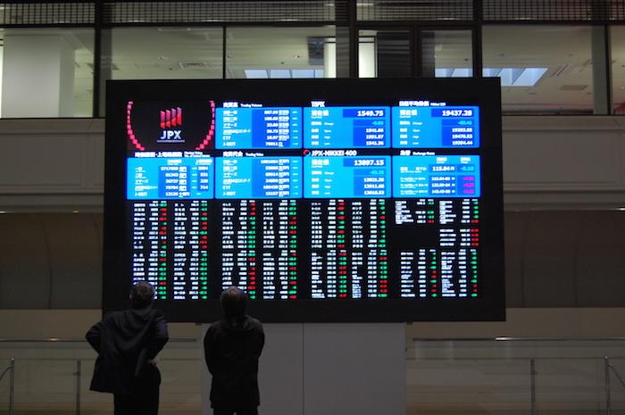 株式ボードを見る投資家